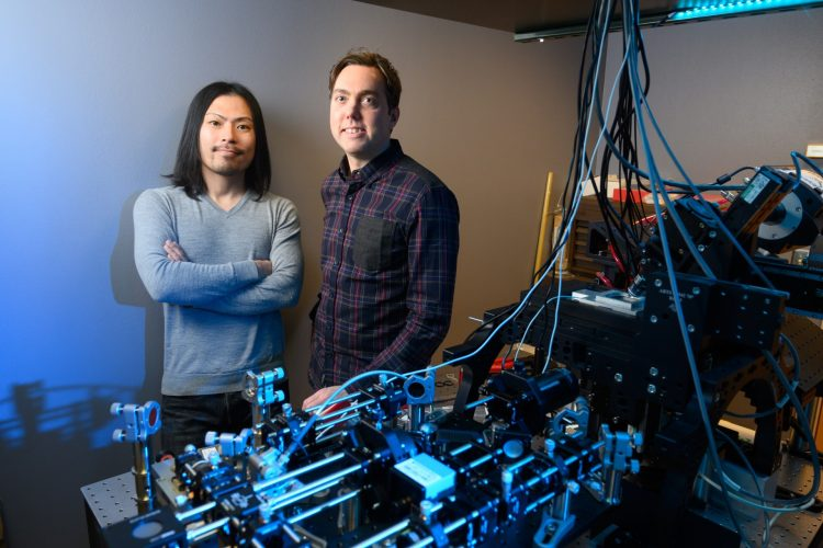 Tim Stasevich (right), Assistant Professor of Biochemistry and Molecular Biology, and Tatsuya Morisaki (left), Research Scientist, with a single-molecule microscope in the W.M. Keck Gene Imaging Lab.